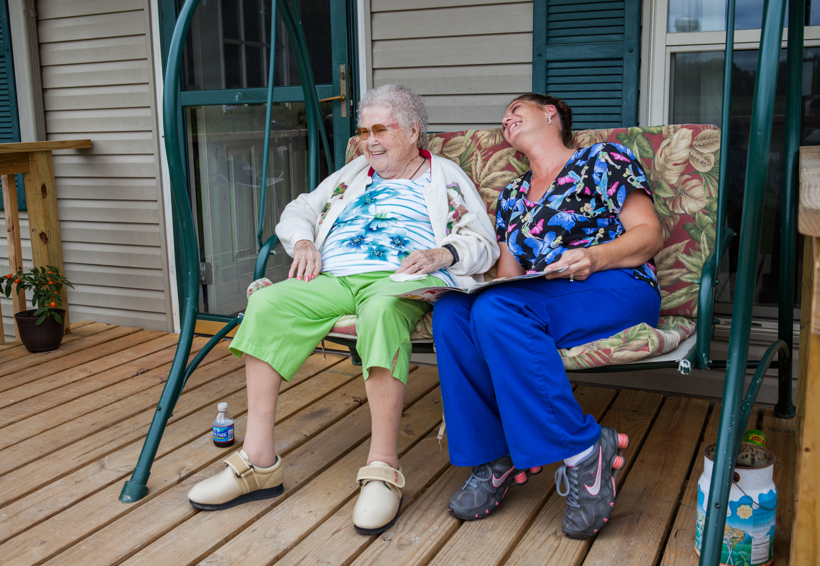 Elderly woman and her caregiver on a porch swing. Laughing, togetherness, happy.