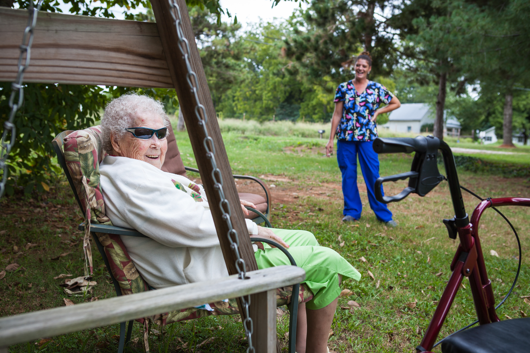 Elderly woman on a swing, wearing funny sunglasses, with her caregiver nearby. Smiling, laughing, happy.