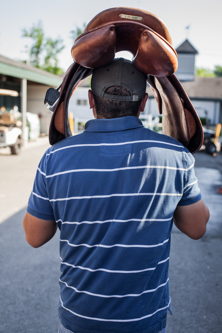 Handler carrying a saddle on his head, Kentucky Horse Show, latino, immigrant, hispanic, worker, authentic, Nashville, documentary, photojournalist, editorial photographer