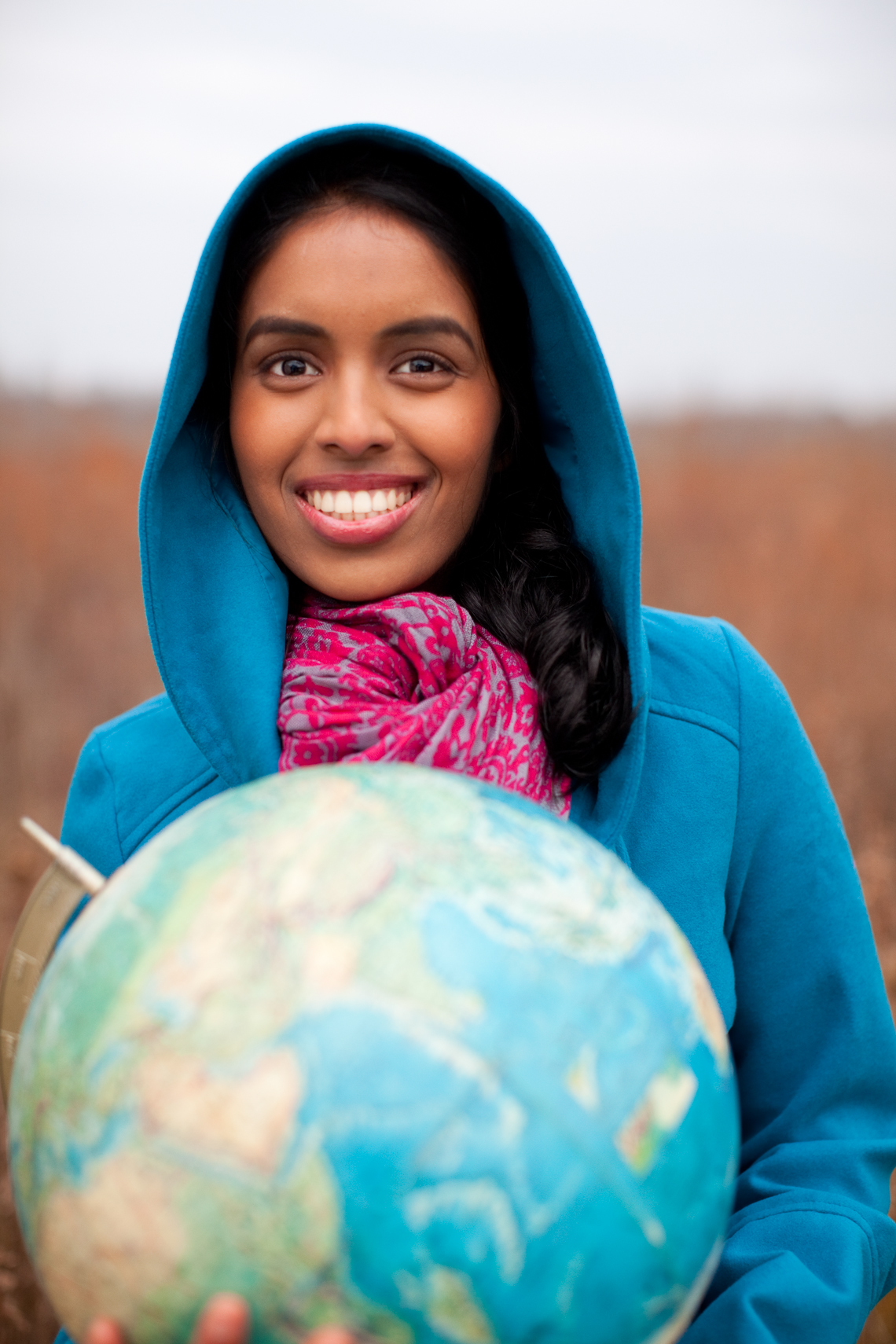 Young Indian girl holding a globe in a bright colorful hood and pink scarf, smiling, teen, happy, standing in a field, Nashville, lifestyle photographer, advertising, stock photo, lifestyle, real life, happy, portrait photographer