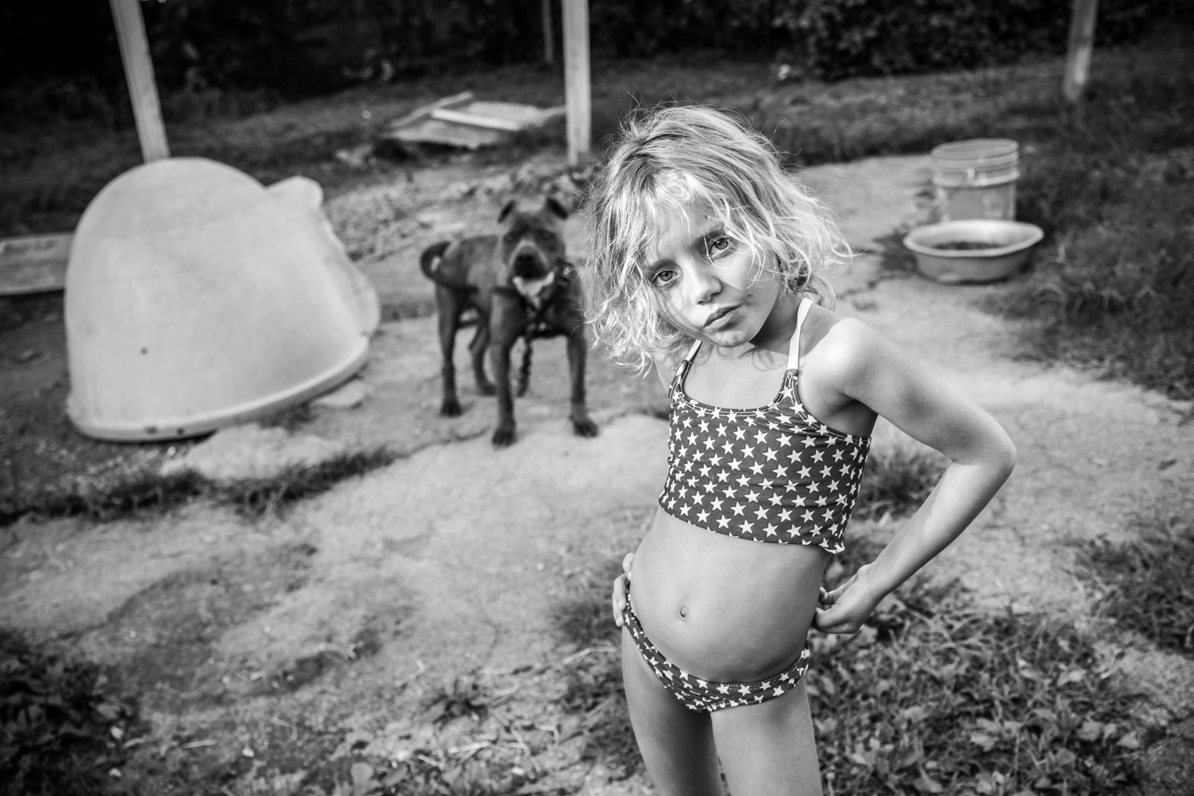 Young girl in with her hand on her hip, swim suit, stars, american, back yard with a big dog on a chain, rural southern life, real life, Nashville, Tennessee. Documentary, Nashville Editorial Photographer, Photojournalist, New Orleans, Nashville, TN, Atla