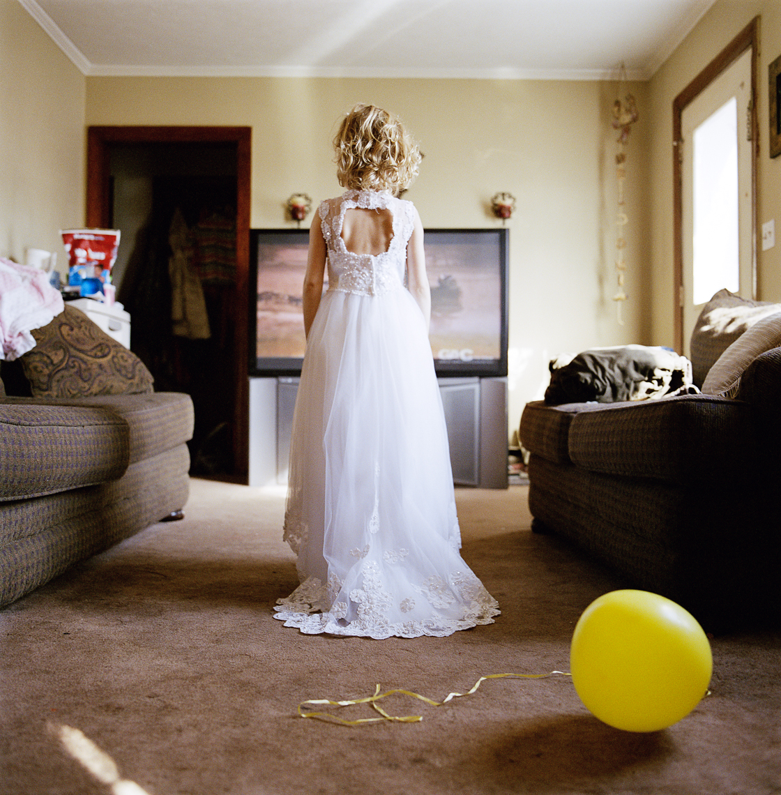 Young girl in a white gown with a yellow balloon watching country music videos in her living room, woman, owned, business, women in photography