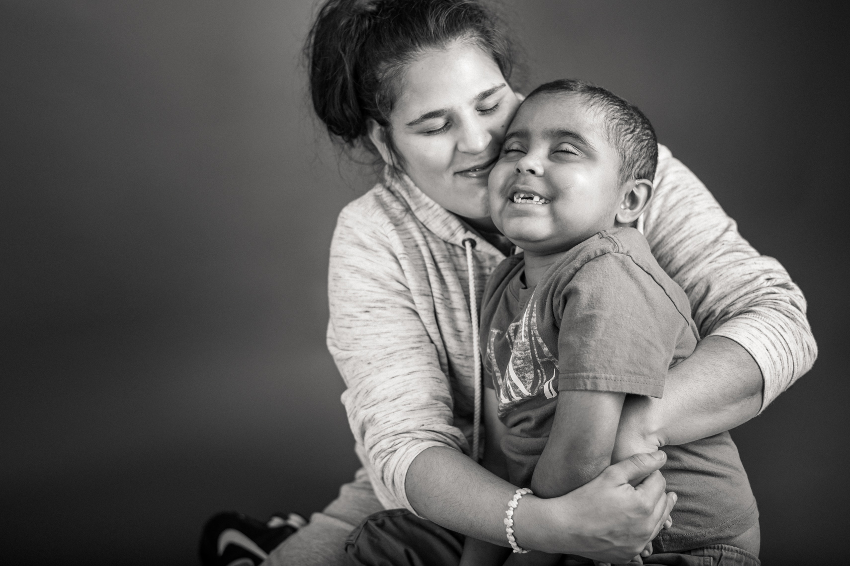 Flashes of Hope, portrait of a young boy batting cancer, being hugged by his mother. Family support, hug, loving, warm, together, resilience, authentic, love, Nashville, portrait, editorial, reportage, news, photographer, portraiture