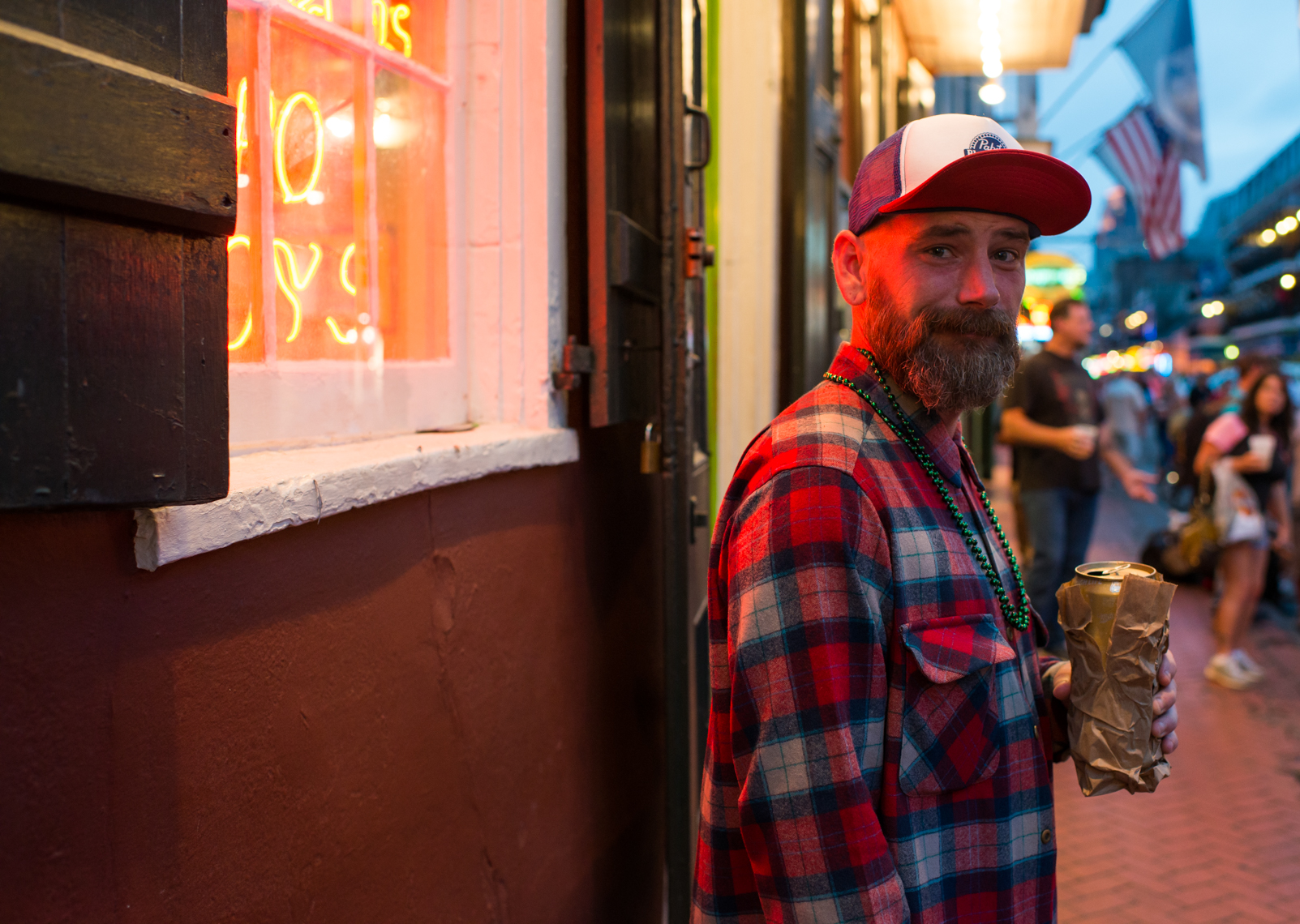 New Orleans, street photography, plaid shirt and PBR ball cap holding beer in a paper bag on Bourbon Street,  Louisiana, liquor, night