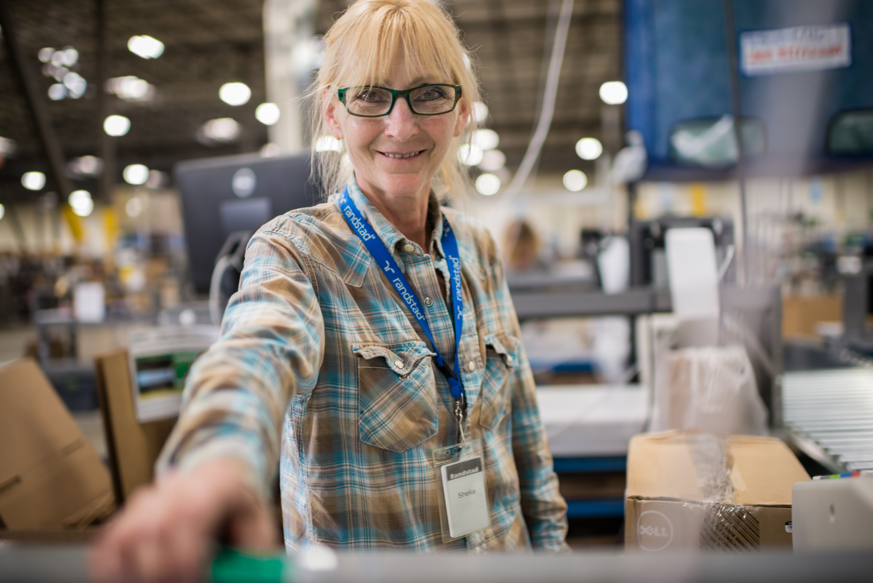 Woman working in the Optoro Warehouse in Mount Juliet, TN. Packaging, portrait, women, golden years, lifestyle, journalism, distribution center, commercial photography.