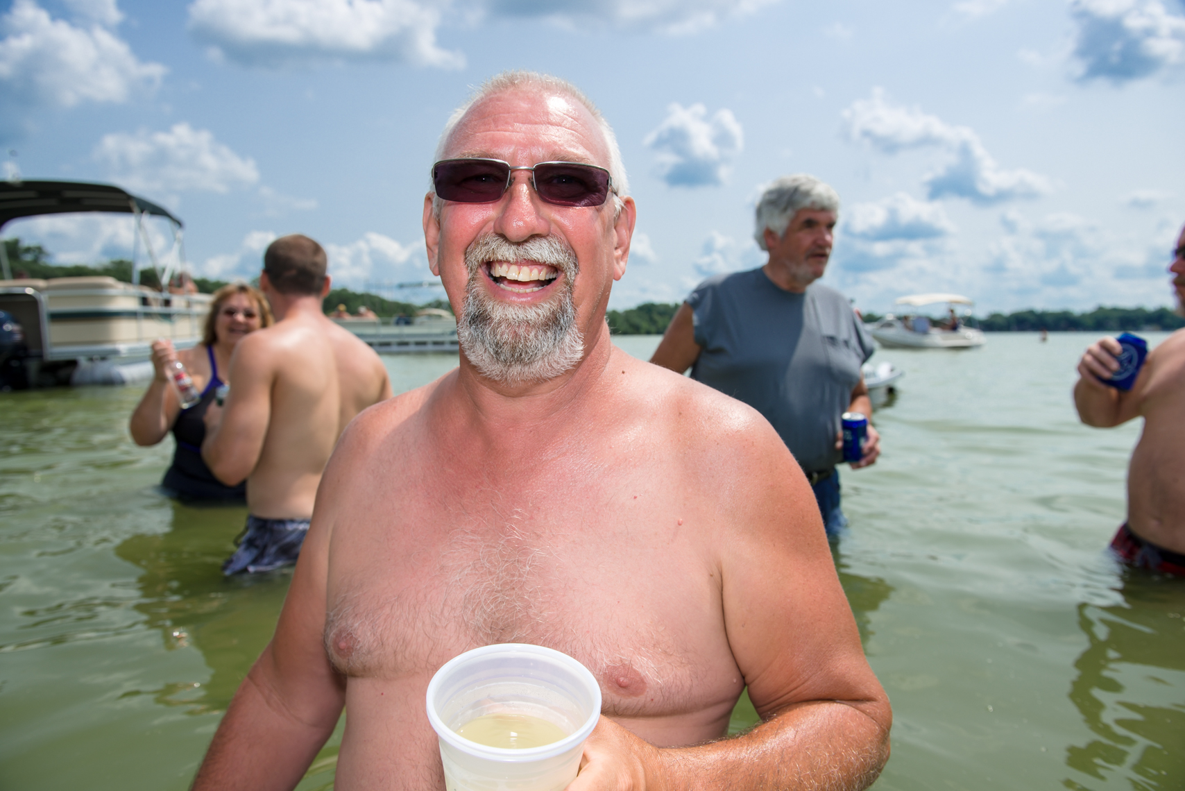Sunburned man with a beer at a lake party in Wisconsin, reportage, swim suit, lake party, fishing, boat, lake party, summer, beverage, swimming, swim, suit, bathing, confident, summer fun, liquor, travel, Madison, Chicago, Nashville advertising, beverage,