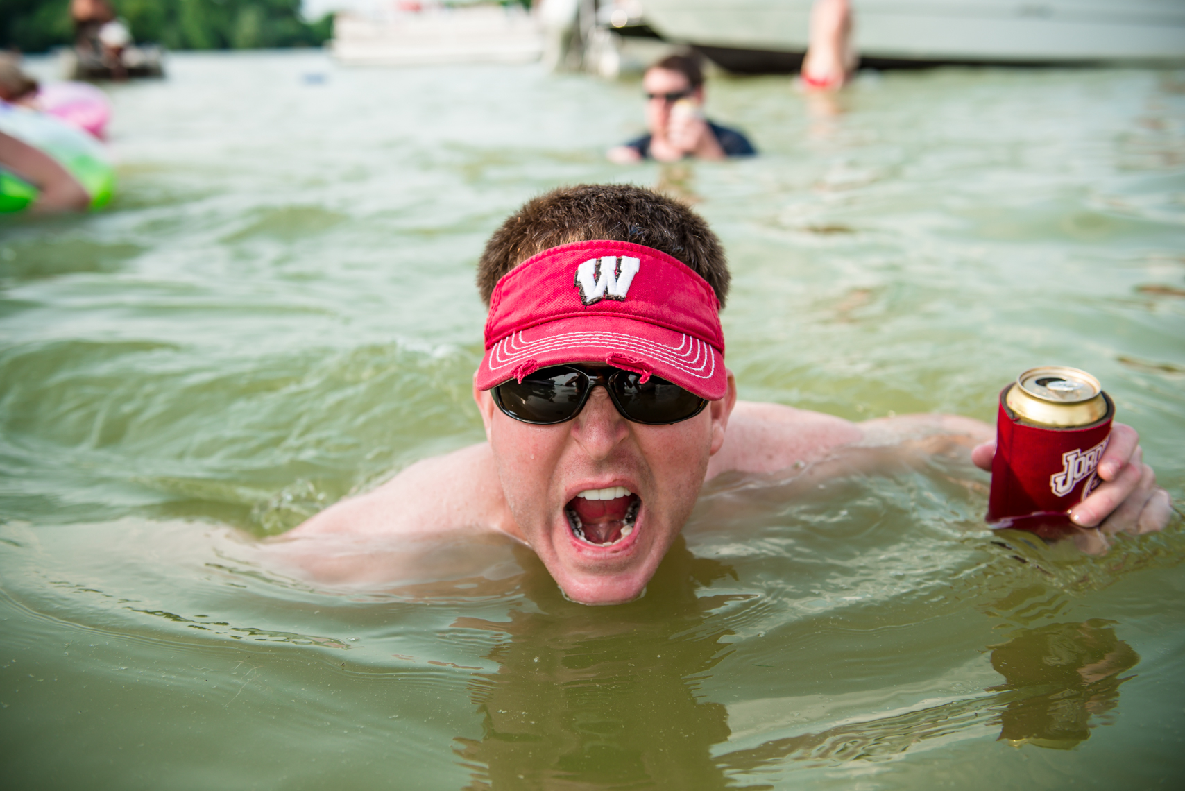 Wisconsin Badgers fan with his beer, funny, goofy, real people, reportage, lake party, summer fun, beverage, swimming, swim, suit, bathing, confident, summer fun, liquor, travel, Madison, Chicago, Nashville advertising, beverage, lifestyle