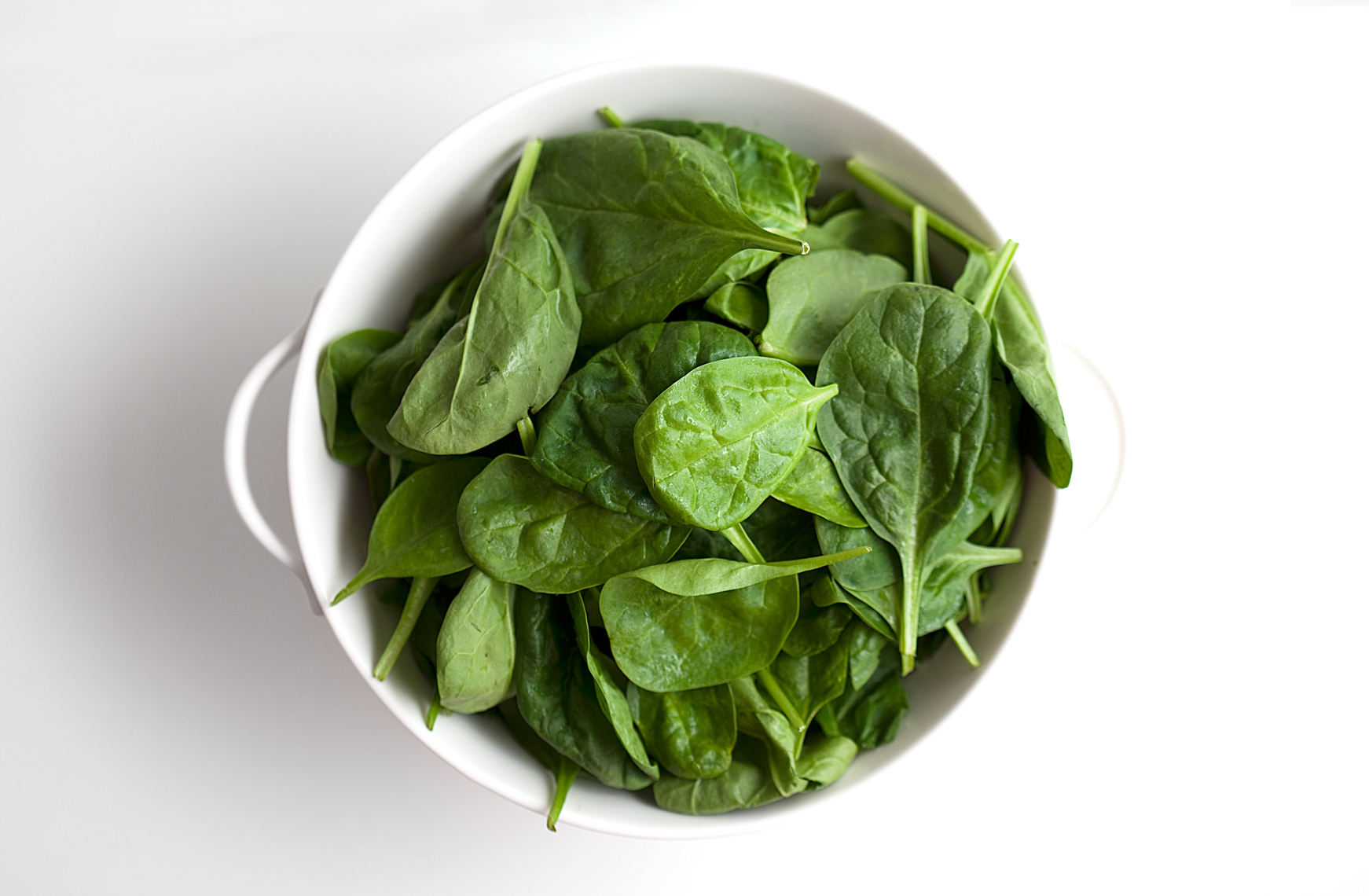 Spinach in a white bowl, white background, silhouette, still life, Nashville food photographer