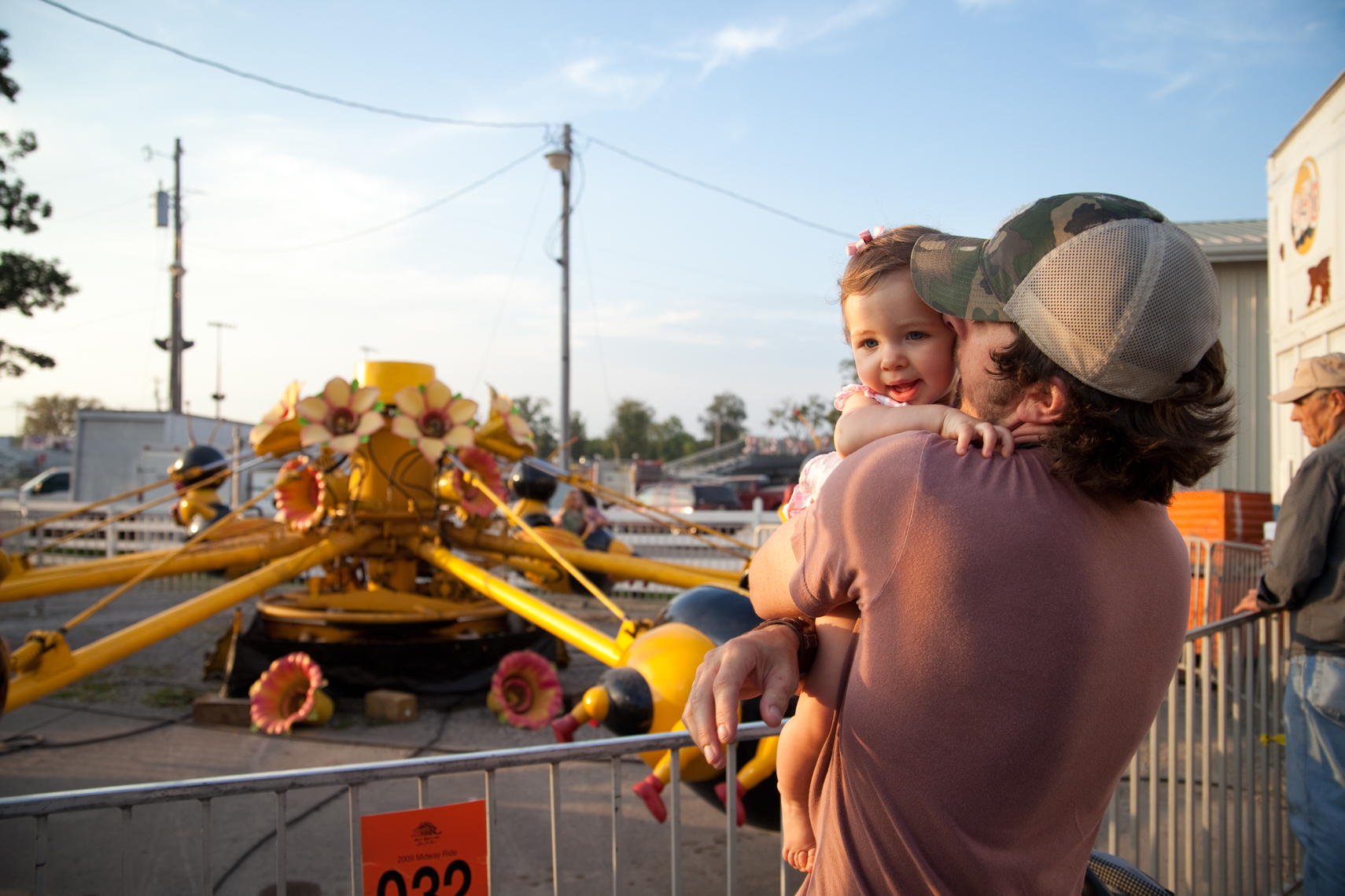 Young father kisses his baby girl on her cheek. Wilson County Fair, Lebanon, Tennessee, carnival, amusement park, rural south, kiss, hug, kissing,Documentary, Editorial, Photojournalist in Nashville, Southeast, South, Texas, Atlanta, New Orleans, Chicago,